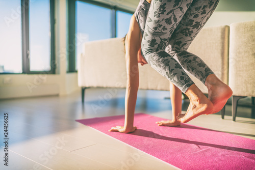 Yoga practicing to handstand - beginner girl doing jump through on hands on exercise mat at home Wallpaper Mural
