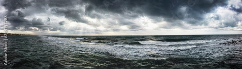 Dramatic weather panorama over the sea threatening waves crashing at the shore with overcast sky and sunbeams on the water -find more in my portfolio