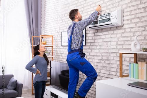 Fotografía  Woman Looking At Technician Repairing Air Conditioner