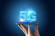 Creative Background, Male Hand Holding A Phone With A 5G Hologram On The Background Of The City. The Concept Of 5G Network, High-speed Mobile Internet, New Generation Networks. Copy Space