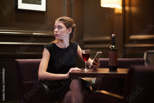 Fotografía  Girl in black dress looking aside while scrolling in smartphone and having red w