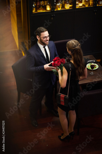 Fotografia Young amorous man giving bunch of roses to girlfriend whle meeting her by table