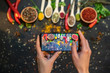 Hands taking photo colourful various herbs and spices with smartphone