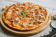 Tasty Pizza Caprizzioza With Tomato Sauce, Ham And Champignons On The White Wooden Background