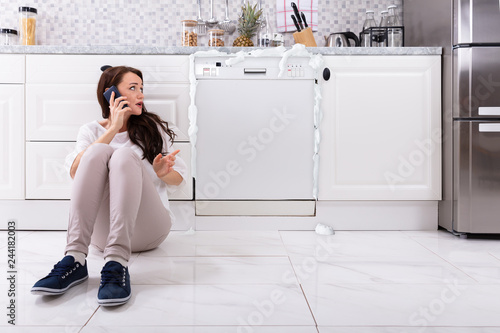 Sad Woman Sitting Next To Damaged Dishwasher Calling Technician Tablou Canvas