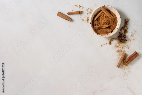 Photo Spices cinnamon powder and sticks, anise star in ceramic bowl over white marble background