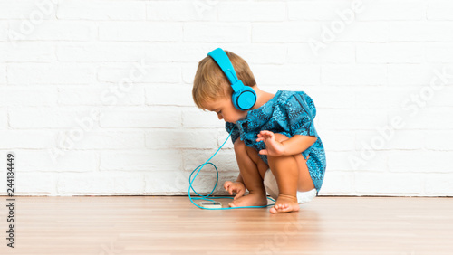 Adorable little baby listening music on white brick background - 244184449