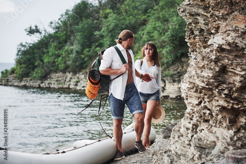 Poster Kaki Cute young and couple on river background. A guy and a girl with backpacks are traveling by boat. Traveler summer concept