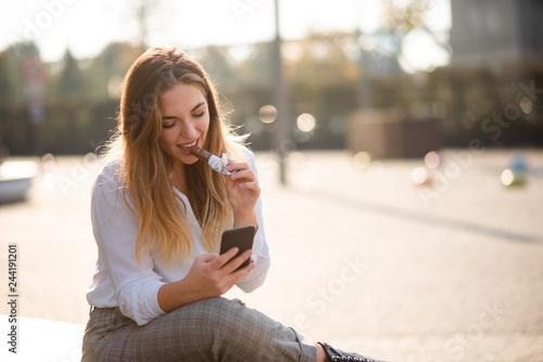 Teenage woman outside chatting on phone, having energy bar. Fototapeta