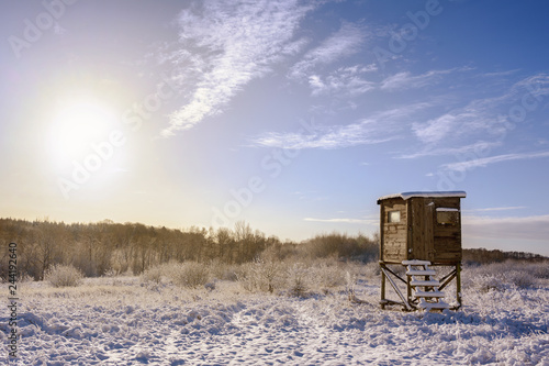 hunter high seat in a snow covered winter landscape against a blue sky with a warm sun, copy space