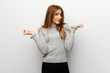 Redhead girl over white wall having doubts while raising hands and shoulders