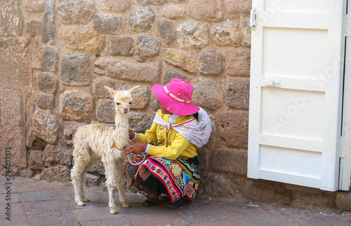 Tuinposter Lama Peruvian little girl in traditional dress with baby llama on the street of Cusco, Peru, Latin America. Horizontal close up. Selective focus