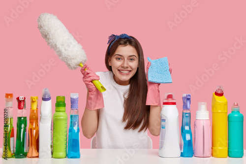 Obraz Joyful dark haired woman carries rag and brush, smiles happily, dressed in casual clothes, sits at white desk with cleaning products, isolated over pink background. Happiness, housekeeping concept - fototapety do salonu