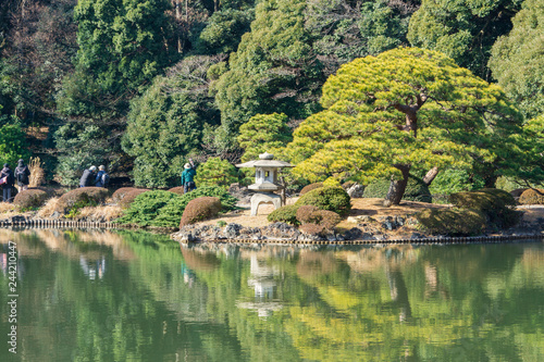 Photo  Tourists and stone lantern and green trees with reflection in water (Japanese ga