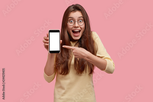 Fotografija  Joyful dark haired woman smiles happily, points at blank screen of cellualr, advertises new gadget, wears round spectacles and casual outfit, isolated over pink background