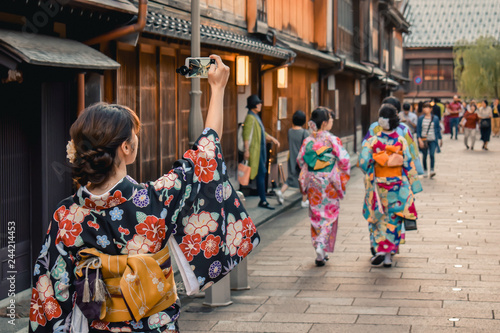 Photo sur Aluminium Kyoto Japanese girl in kimono taking a photo of a traditional street with wooden houses on her cell phone in Kanazawa Japan