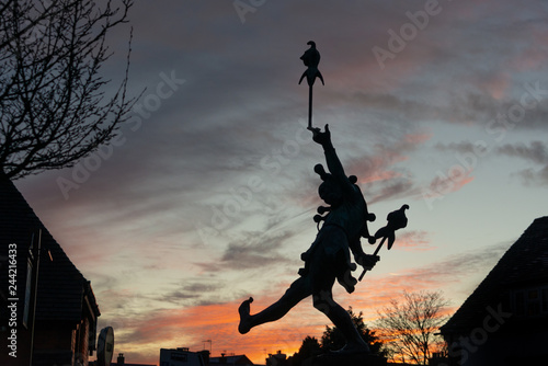 Canvas Prints Military silhouette of court jester or imp toy dancing over rooftops