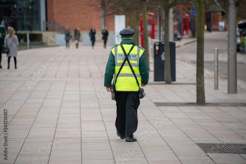 Photo traffic warden civil enforcement officer wearing reflective yellow vest walks do