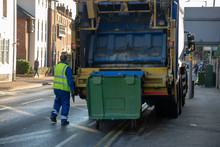Bin Lorry Or Waster Truck Collects Refuse From A Green Dumpster With Council Bin Worker Operating Mechanism In A Yellow Vest