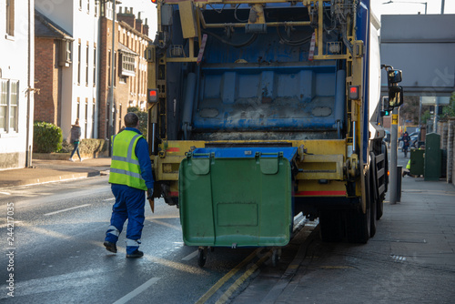 bin lorry or waster truck collects refuse from a green dumpster with council bin Fototapeta