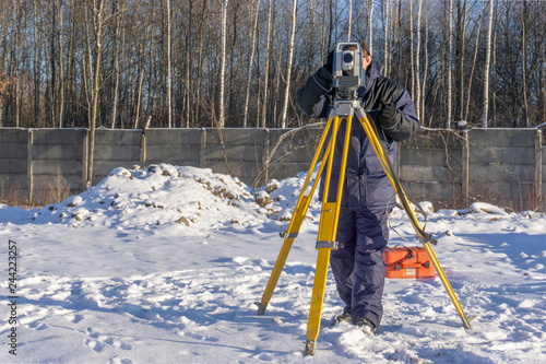 Surveyor conducts a topographical survey for the cadastre at a construction site in winter