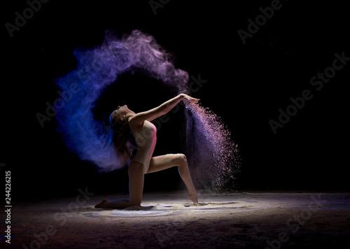 Fotografía  Brunette on her knees in color dust in the dark