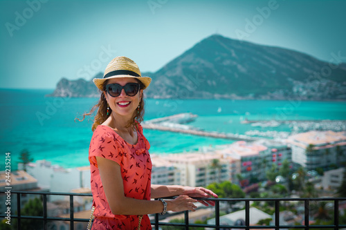 Foto Happy tourist woman with straw sunhat looking to the mediterranean sea and enjoying the blue and scenic seascape in Altea, Alicante, Spain