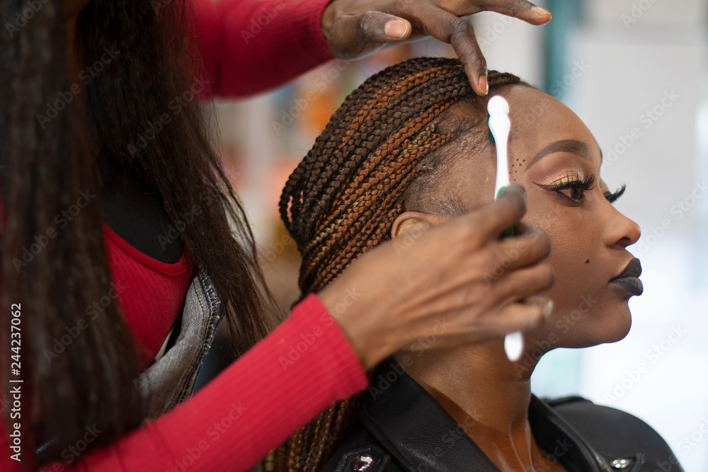 Fototapety, obrazy: A black hairstylist combing with a toothbrush a beautiful black model.
