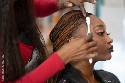 Obraz A black hairstylist combing with a toothbrush a beautiful black model. - fototapety do salonu