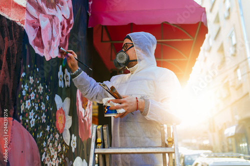plakat Young graffiti artist painting mural outdoors on street wall.