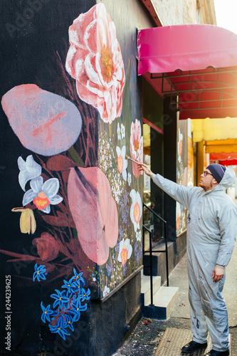 obraz dibond Young graffiti artist painting mural outdoors on street wall.