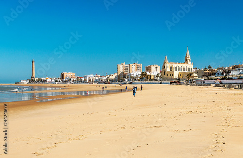 Chipiona, Cadiz, Spain-June 2016. Tourists walking along the beach of the turistic municipality of the coast of light in Cadiz on a sunny day.