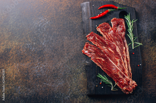 Fotografie, Obraz  Raw sliced beef bacon ready for cooking on dark black concrete background