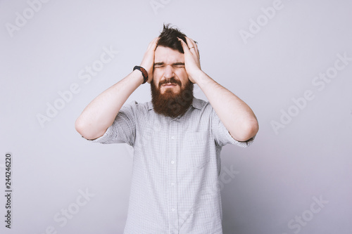 Fotografía  Portrait of trouble worried handsome bearded pressing hands to heat, forgetting