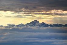 Jagged Snowy Triglav Peak Of Julijske Alpe Range Towering Dramatically Over Sea Of Low Clouds With Sky In Glowing Orange Light Behind, Triglav National Park Gorenjska Kranjska Carniola Slovenia Europe