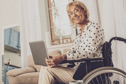 Valokuva  Positive delighted invalid woman working with laptop