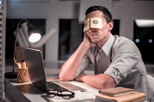 Fotografia Pleasant tired man sitting at the table in the office