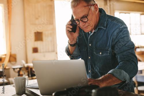 Fototapeta Senior male carpenter on the phone