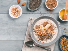 Overnight Oats In Bowl And Ingredients - Banana, LSA, Chia Seeds, Almond, Honey And Pollen On Gray Wooden Table Background. Healthy Breakfast Oatmeal Recipe Idea. Top View. Copy Space