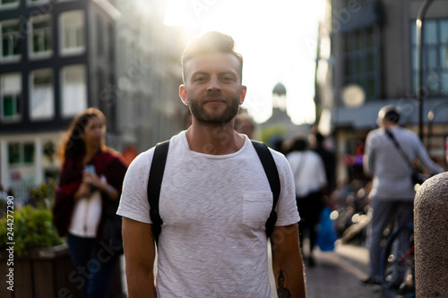 A man with a backpack walks through the streets of Amsterdam. Canvas Print