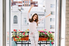 Happy Young Girl In Pajamas Having Fun On Balcony In Sunny Morning. She Raises Hands And Keeps Eyes Closed