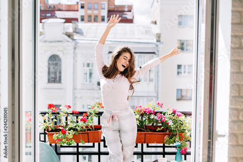 Happy young girl in pajamas having fun on balcony in sunny morning Wallpaper Mural
