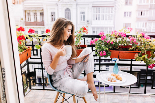 Fototapeta Attractive girl with long hair in pajama having breakfast on balcony in the morning in city