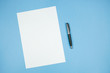White paper sheet with pen on blue background.