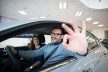 Happy Customer Buying New Car At Dealership. New Vehicle Good Deal.