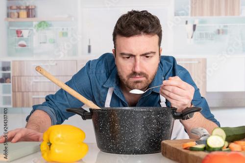 Fototapeta Concentrated young man preparing food at home obraz