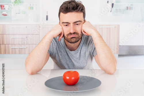 Fotografie, Tablou  Worried man hungry and starved with salad