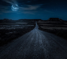 Moon, Stars And Clouds In The Night. Wild West Road Illuminated From The Moon. Moonlight And Road Background.