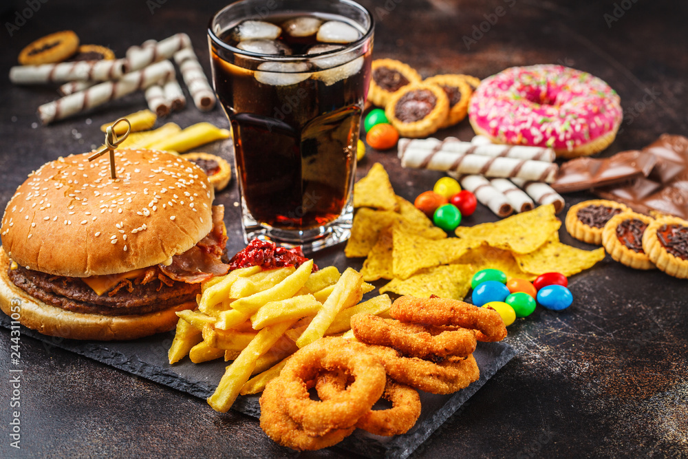 Fototapety, obrazy: Junk food concept. Unhealthy food background. Fast food and sugar. Burger, sweets, chips, chocolate, donuts, soda.