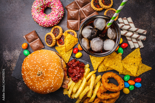 Fototapeta Junk food concept. Unhealthy food background. Fast food and sugar. Burger, sweets, chips, chocolate, donuts, soda, top view. obraz